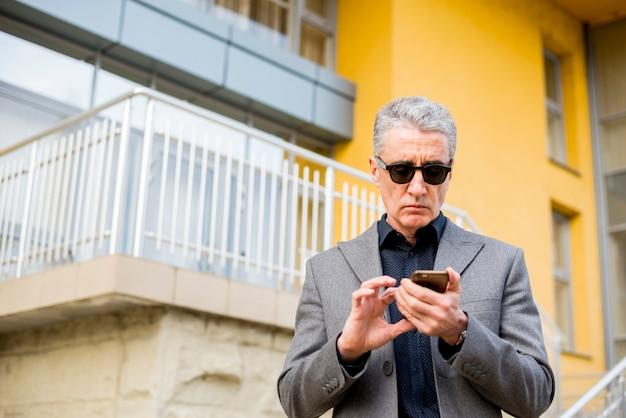 Idoso, homem negócios, com, telefone móvel Foto gratuita
