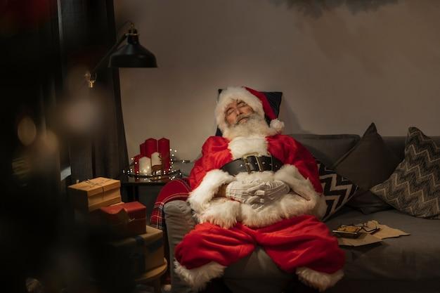 Idoso papai noel dormindo no sofá Foto gratuita
