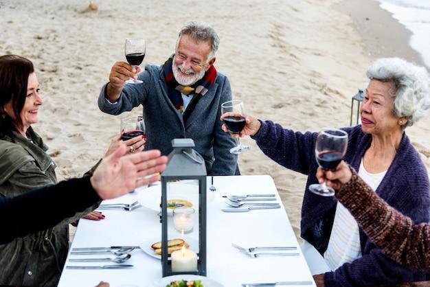 Idosos brindando com vinho tinto na praia | Foto Premium