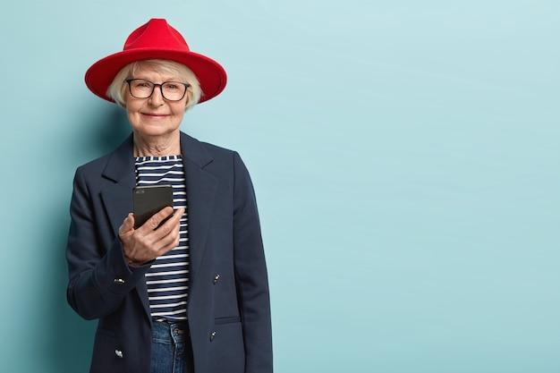 Idosos e conceito de tecnologia. mulher idosa está sempre conectada, conversa via app, envia mensagens, usa capacete vermelho, macacão listrado com jaqueta formal, isolado sobre parede azul Foto gratuita