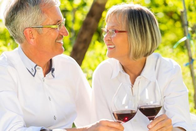 Idosos sentados na vinha bebendo vinho tinto | Foto Premium