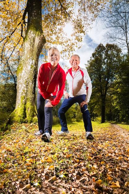 Idosos treinando em uma estrada da floresta Foto Premium