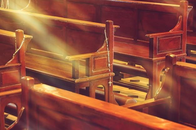 Igreja de madeira bancos na igreja e rosário com luz solar Foto Premium