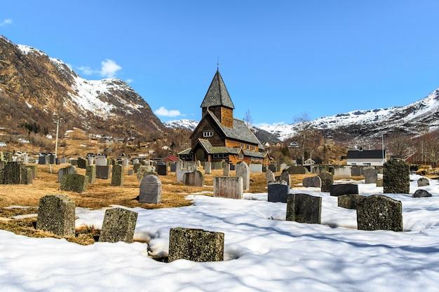 Igreja de madeira roldal (roldal stavkyrkje) com primeiro plano de cemitério de neve Foto Premium