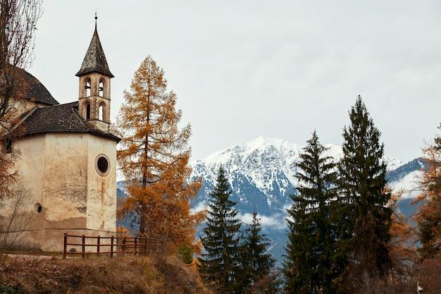 Igreja e floresta de outono colorida com montanhas Foto Premium