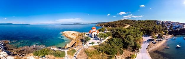 Igreja e mar com praia e montanhas em nea roda, halkidiki, grécia Foto Premium