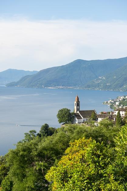 Igreja em ronco sopra ascona no lago maggiore alpino com montanha Foto gratuita