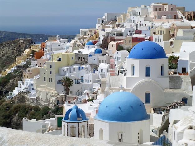 Ilhas gregas estilo branco e azul igrejas na vila de oia, ilha de santorini, grécia Foto Premium