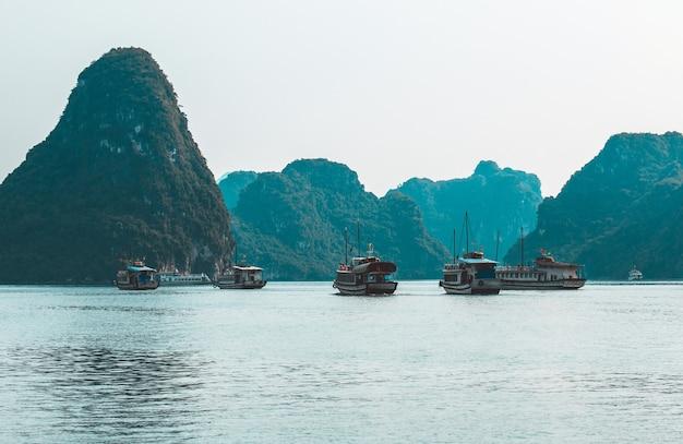 Ilhas rochosas perto de uma vila flutuante na baía de halong. bela paisagem do mar na baía de ha long, vietnã Foto Premium
