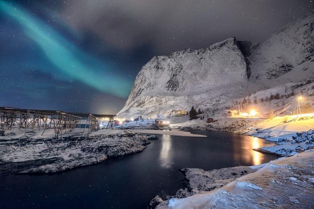 Iluminação da aldeia escandinava com luzes do norte brilhando na montanha de neve Foto Premium