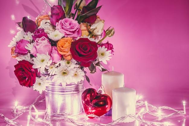 Iluminação vaso de buquê rosas, coração vermelho e vela branca Foto Premium