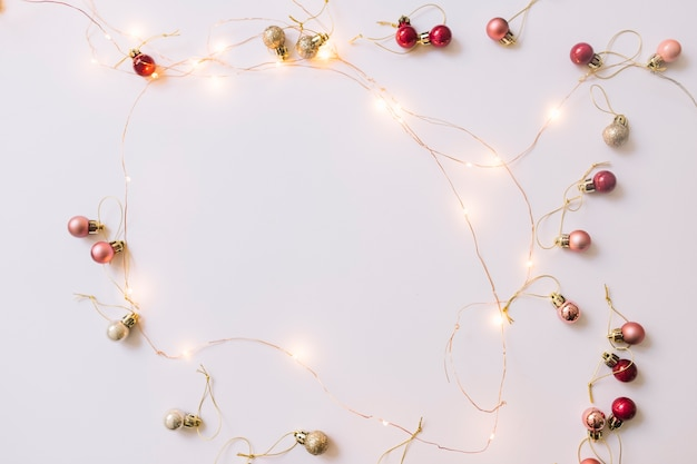 Iluminando as luzes de fada perto de enfeites de natal Foto gratuita