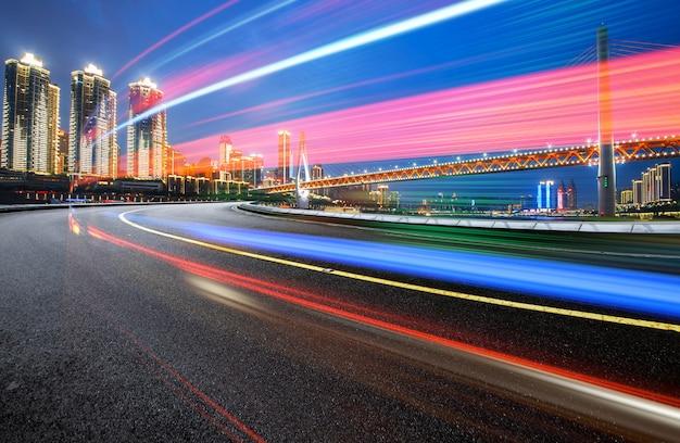 Imagem abstrata do movimento borrão de carros na estrada da cidade à noite, arquitetura urbana moderna em chongqing, china Foto Premium
