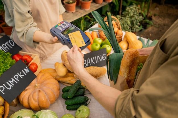 Imagem acima de um cliente irreconhecível colocando o cartão de crédito no terminal enquanto paga por alimentos orgânicos no mercado do fazendeiro Foto Premium