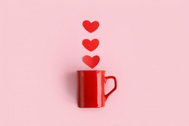 Imagem aérea da vista superior da mesa do conceito de plano de fundo dia dos namorados de sinal. copo de café vermelho arranjo plano leigos com forma de coração de vapor no estúdio de mesa-de-rosa moderno papel rosa em casa. Foto Premium
