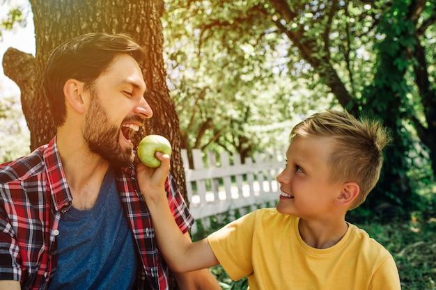 Imagem bonita de pai e filho sentados juntos lá fora debaixo da árvore. garoto está segurando uma maçã enquanto seu pai está mordendo um pedaço dela. Foto Premium