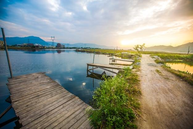 Imagem bonita do céu do sol atrasado sobre a paisagem do lago calmo com ca Foto gratuita
