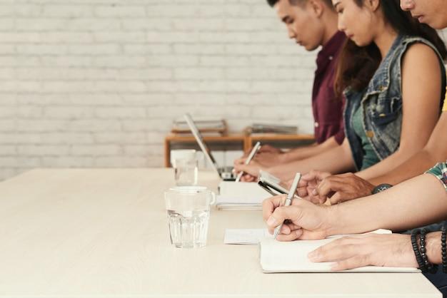 Imagem borrada da linha de estudantes ocupados escrevendo teste em sala de aula Foto gratuita