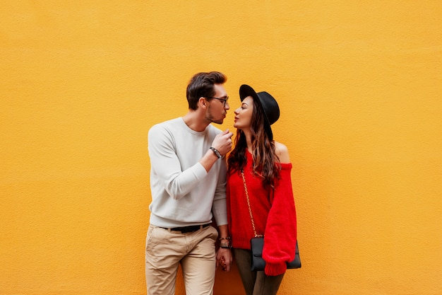 Imagem brilhante de amantes posando na parede amarela. olhar na moda. humor romântico. de mãos dadas. jovem mulher com um sorriso sincero flertando com o namorado. bolsa de luxo. Foto gratuita