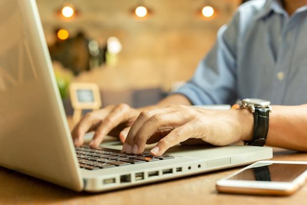 Imagem colhida do homem de negócios que trabalha em seu portátil em uma cafetaria. Foto Premium