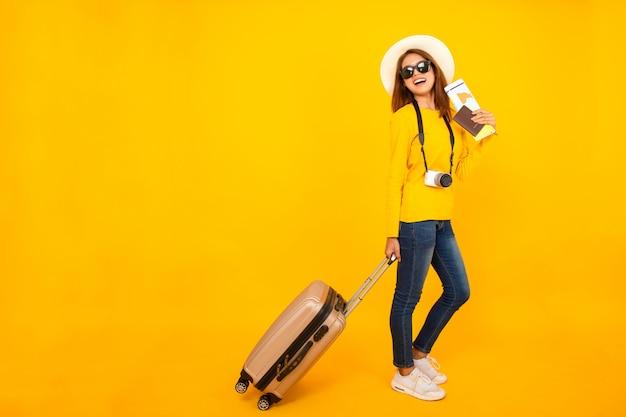 Imagem completa, mulher asiática do viajante bonito com câmera e bagagem isolada no fundo amarelo. Foto Premium