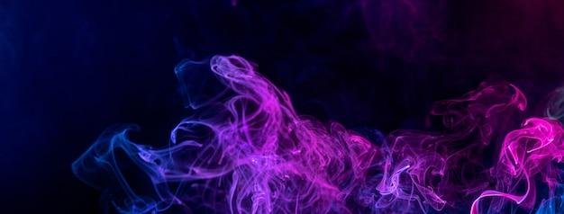 Imagem conceitual de fumaça colorida de vermelho e azul isolada em fundo preto escuro, elemento de design de conceito de halloween. Foto Premium
