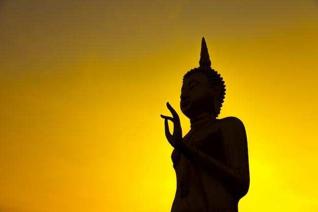 Imagem da silhueta de buda no céu do sol dourado Foto Premium