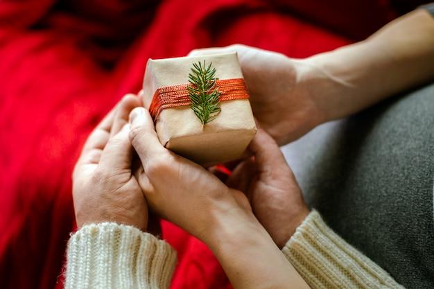 Imagem da vista superior da mão masculina e fêmea com caixa de presente. conceito de celebração familiar de natal e ano novo. Foto Premium