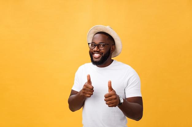 Imagem de alegre jovem africano em pé e posando sobre fundo amarelo com polegares para cima Foto Premium