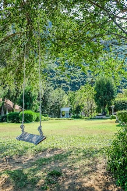 Imagem de balanço de madeira debaixo da árvore no jardim Foto Premium