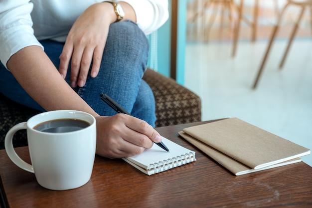 Imagem de close de uma mão de mulher escrevendo em um caderno em branco com uma xícara de café na mesa de madeira Foto Premium