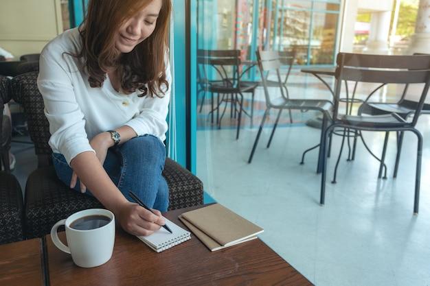 Imagem de close de uma mulher escrevendo em um caderno em branco com uma xícara de café na mesa de madeira Foto Premium