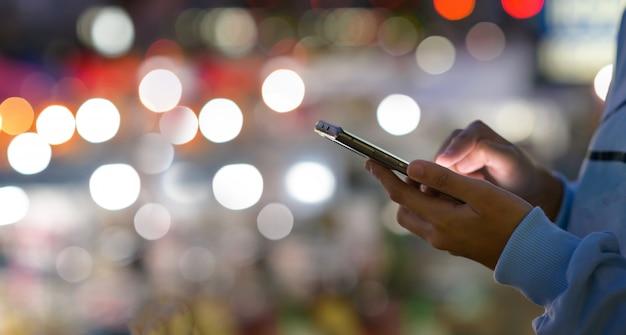 Imagem de close-up de mãos de mulheres usando o smartphone à noite na rua comercial da cidade, busca ou conceito de redes sociais, homem hipster digitando uma mensagem sms para seus amigos Foto Premium