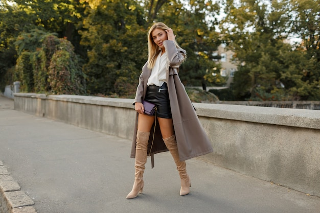 Imagem de corpo inteiro da moda de uma mulher loira elegante em um luxuoso casaco de couro bege e salto alto, caminhando ao ar livre Foto gratuita