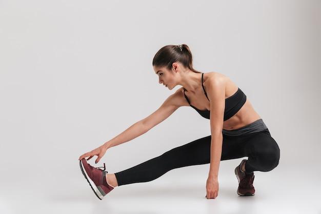 Imagem de corpo inteiro de mulher desportiva com corpo flexível de cócoras e esticando a perna, isolada sobre parede cinza Foto Premium