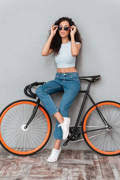 Imagem de corpo inteiro de mulher muito encaracolada em óculos de sol posando com bicicleta sobre fundo cinza Foto gratuita