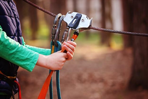 Imagem de esportes de escalada de um mosquetão em uma corda de metal em uma floresta Foto Premium