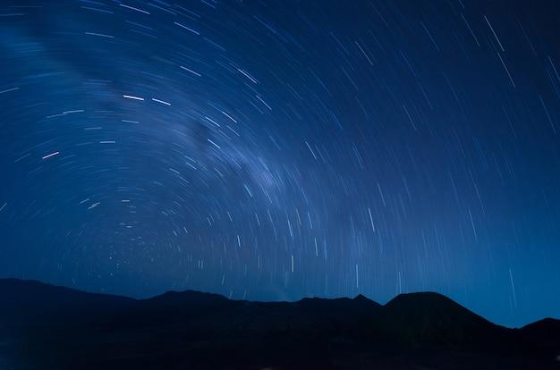 Imagem de extrema longa exposição mostrando fugas estrela acima do vulcão bromo, indonésia Foto Premium