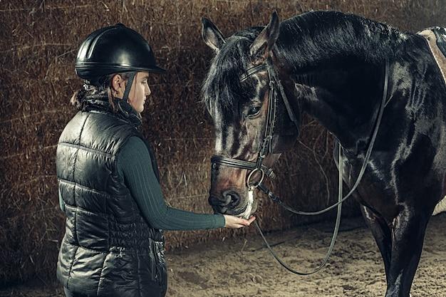 Imagem de feliz feminino em pé próximo no cavalo de raça pura Foto gratuita