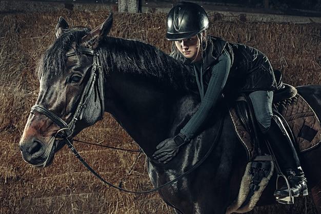 Imagem de feliz feminino sentado no cavalo de raça pura Foto gratuita