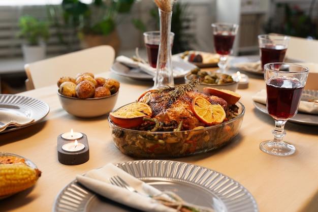 Imagem de fundo de um delicioso frango assado na mesa de ação de graças, pronto para um jantar com amigos e família Foto Premium