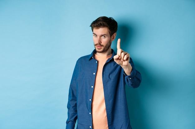 Imagem de jovem dar aviso, dando uma lição, levantando um dedo para repreender, olhando para a câmera, tratando com condescendência alguém, de pé sobre fundo azul. Foto Premium