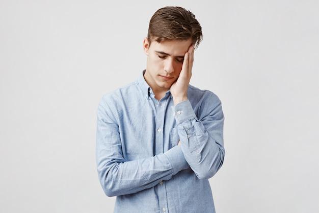 Imagem de jovem exausto em camisa casual azul. Foto gratuita