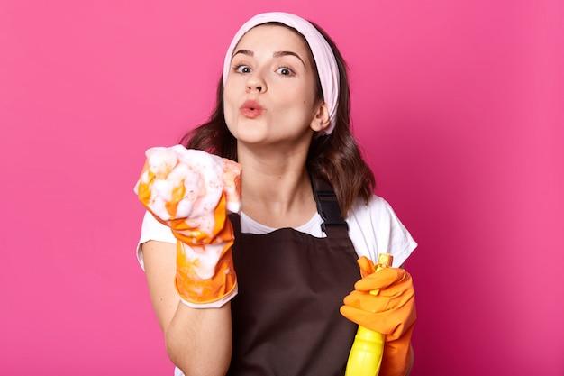 Imagem de jovens com expressão facial agradável, veste camiseta e avental, parece feliz, enquanto faz tarefas domésticas, segurando spray e sopra espuma da esponja. conceito de higiene, limpeza e limpeza. Foto Premium