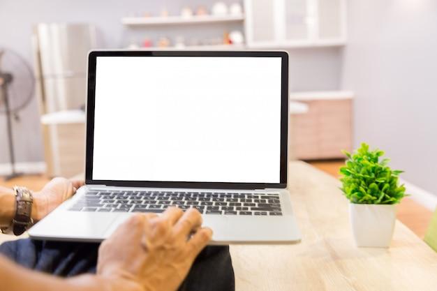Imagem de maquete de um empresário usando laptop com tela branca em branco, trabalhando em casa Foto Premium