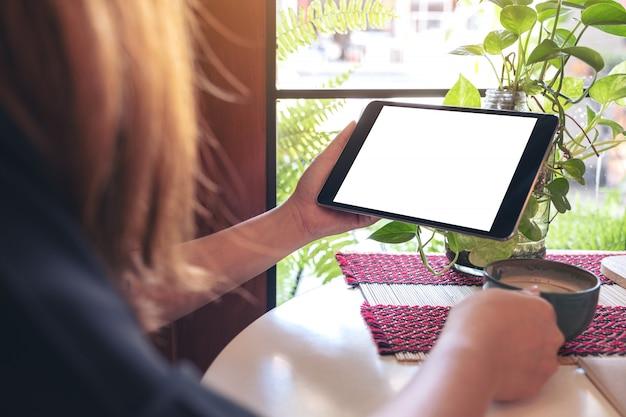 Imagem de maquete de uma mulher segurando um tablet pc preto com uma tela branca em branco Foto Premium