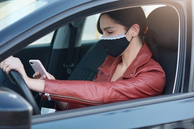 Imagem de menina com cabelos escuros e rabo de cavalo, veste jaqueta de couro e máscara protetora, segurando o telefone nas mãos Foto Premium