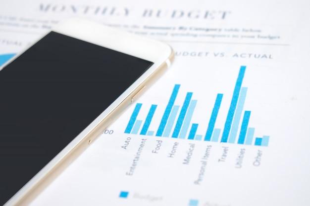 Imagem de mesa de escritório moderno com smartphones no gráfico financeiro de empresários Foto Premium