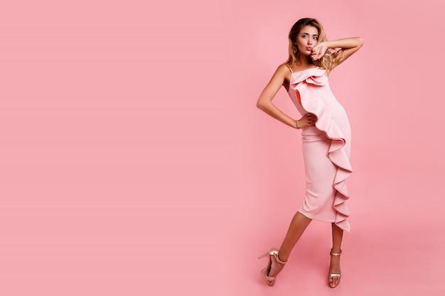 Imagem de moda altura total da mulher loira com penteado ondulado perfeito no vestido de festa rosa posando. saltos altos. cara de surpresa. espaço para texto. Foto gratuita