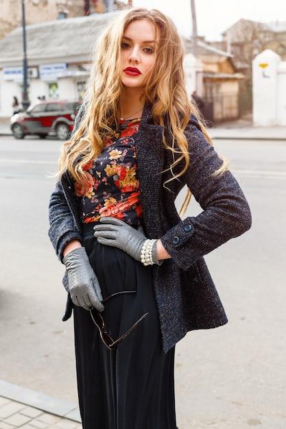 Imagem de moda ao ar livre de uma mulher bonita e elegante com cabelos loiros encaracolados e grandes lábios carnudos brilhantes, posando na rua, vestindo um casaco quente elegante. retrato de outono. Foto gratuita